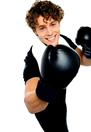 Young man with black boxing gloves and aggressive action photo