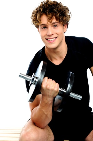 Fit trainer doing biceps exercise against white background photo