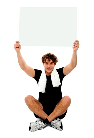 towel wrapped: Handsome athlete holding blank placard over his head. Towel wrapped around neck Stock Photo