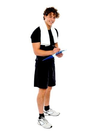body writing: Full length portrait of male fitness trainer preparing dieting chart