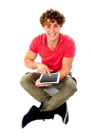 the latest models: Smiling young guy using his tablet pc. Touch-screen technology
