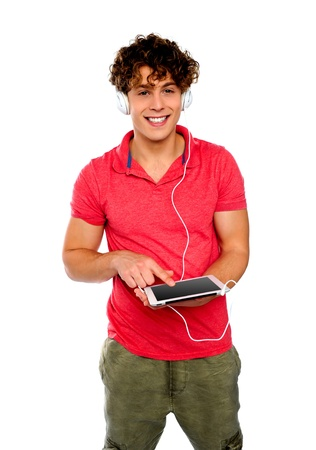 Guy enjoying music having headphones attached to tablet photo