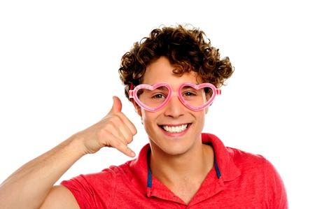 Boy posing with heart shaped eye-wear gesturing call