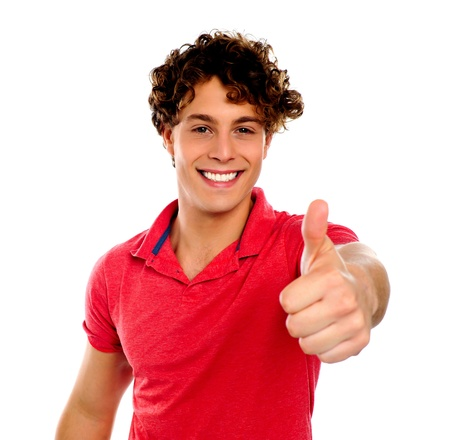 Handsome young man gesturing thumbs-up isolated on white Stock Photo - 13823442