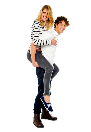 carrying girl: Boyfriend giving piggy ride to his girl isolated on white background Stock Photo