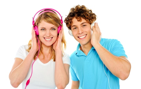 Couple enjoying music through headphones isolate over white photo