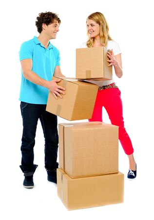 Happy young couple moving cardboard boxes smiling with eye contact photo