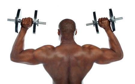 Rear view of a young male bodybuilder doing heavy weight exercise with dumbbells photo