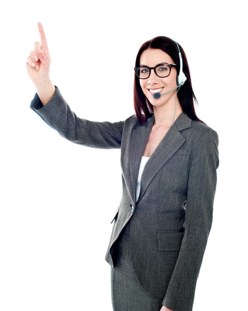 Beautiful customer care executive pointing up at copyspace over white background photo