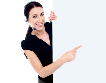 customercare: Customer service woman with headset showing and pointing at blank billboard sign banner