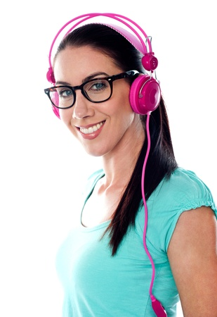 tuned: Pretty girl tuned into listening music via headphones isolated on white background