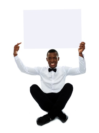 Seated black man pointing towards blank billboard over his head photo