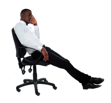 Portrait of thoughtful young businessman sitting on chair photo
