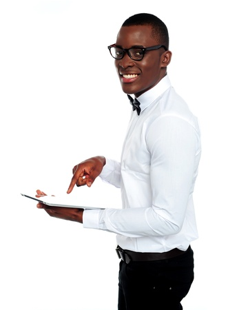 Smiling african operating touch-pad device wearing glasses photo