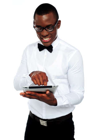 electronic devices: Smiling african boy with eyeglasses having fun with tablet-pc isolated over white