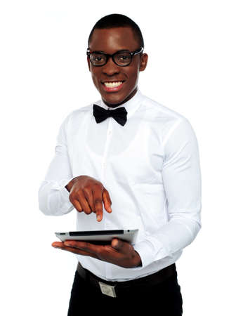 Smart boy using touch screen device smiling in front of camera photo