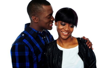 Portrait of handsome young african man whispering in his girlfriends ear photo