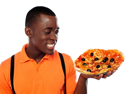 Smiling young black man holding yummy pizza against white background photo