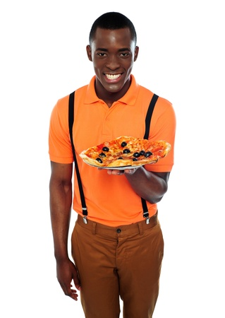Smiling young african boy offering delicious pizza isolated against white background photo