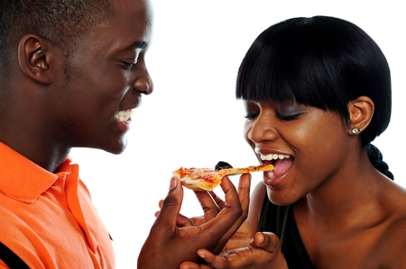 over eating: Beautiful african couple eating pizza isolated over white, closeup shot Stock Photo