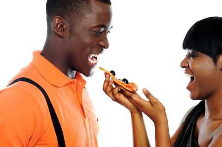 Gorgeous girl offering pizza to handsome guy photo
