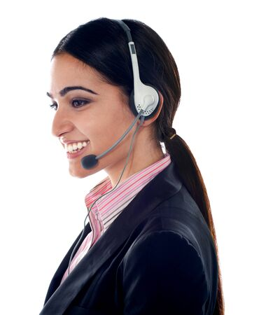 Side pose of pretty female customer care executive wearing headsets photo