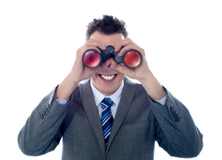 Smiling businessman looks through binoculars and seeks success. All on white background photo