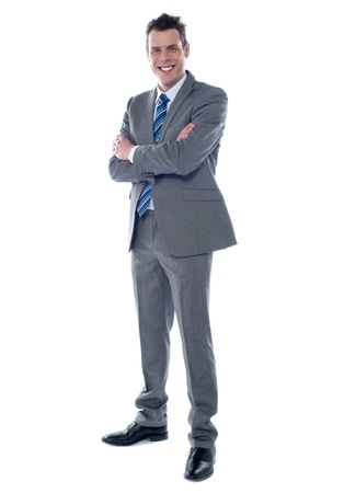 Smiling businessman standing with arms crossed against white background photo