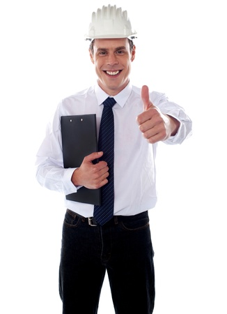 Cheerful architect gesturing thumbs up wearing hard hat and holding clipboard Stock Photo - 14087679