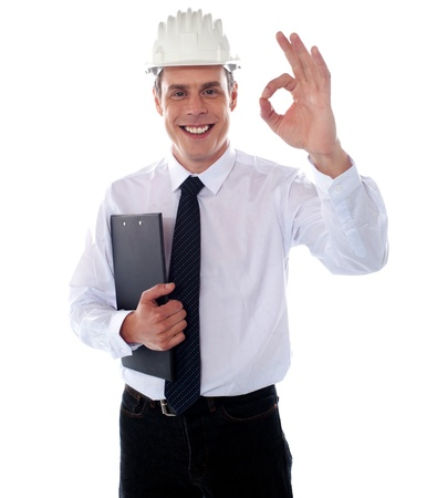 posing  agree: Handsome engineer showing okay gesture wearing safety helmet and holding clipboard Stock Photo