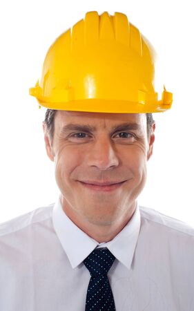 An architect wearing yellow safety helmet looking confidently at camera photo