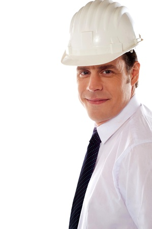 Smiling male architect wearing hard hat and smiling at camera photo