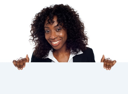 Portrait of happy young woman holding blank billboard against white background photo