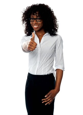 Confident woman showing thumbs up gesture to camera. Wearing glasses photo