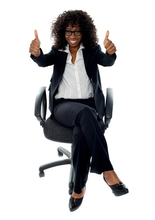 Business woman giving double thumbs up to camera while sitting relaxed on chair photo