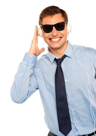 Casual young man listening music on headphones wearing sunglasses photo