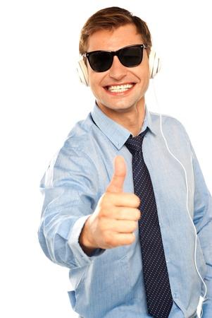 eye wear: Happy young man enjoying music showing thumbs up. Wearing black eye wear