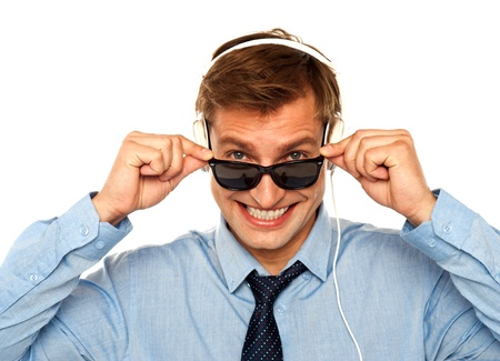 Musical guy peeping from sunglasses isolated against white background photo