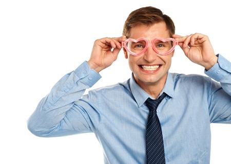 eye wear: Smiling young man wearing heart shaped eye wear isolated on white