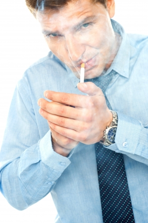 Young man lighting a cigarette against white background photo