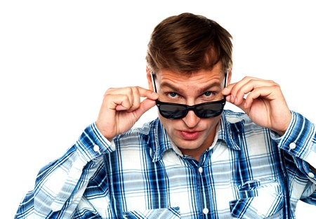 Confident young man peeping from behind the goggles right into camera photo