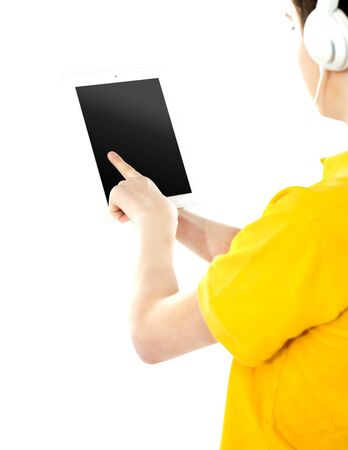 Boy operating touch pad device and wearing headphones photo