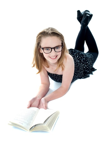 Smiling little girl lying with an open book on floor. All on white background photo