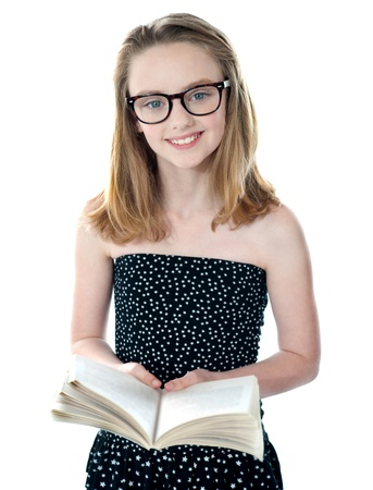 Cute little girl standing with an open book. Smiling at camera photo
