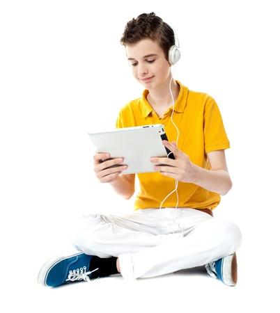 Boy sitting with crossed legs watching video on tablet photo