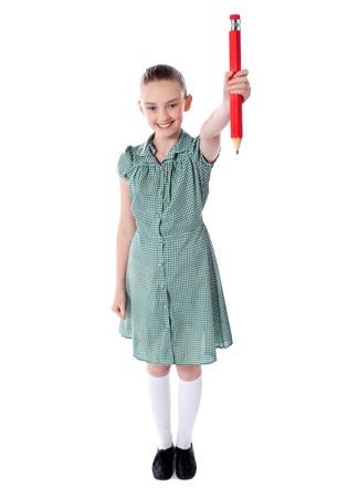 niños con lÁpices: Atractiva chica de pie mostrando gran lápiz rojo sobre fondo blanco
