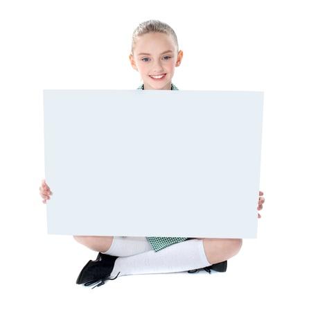 ni�os con pancarta: Ni�a de la escuela mostrando cartelera en blanco a la c�mara aislado m�s de blanco Foto de archivo