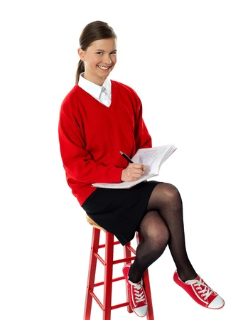 Confident girl doing her homework as she rests on stool. All on white background Stock Photo - 14161690