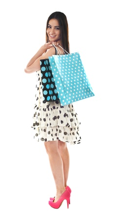 Stunning teenager carrying shopping bags on her shoulder isolated over white photo