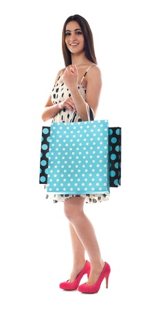Glamorous female carrying shopping bags isolated over white photo